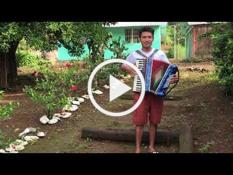 Eraclio playing music at his jungle village
