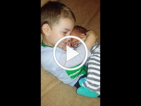 Little Boy Snuggles Newborn Baby Brother